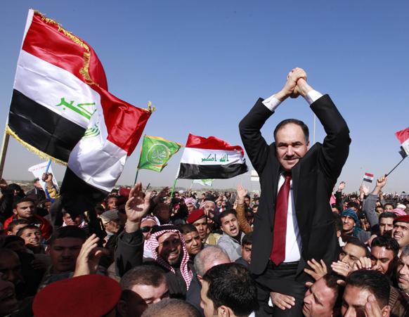 इराक के बगदार में एक प्रदर्शन के दौरान वित्त मंत्री राफिया अल इसावी को कंधे में उठाए हुए समर्थक।