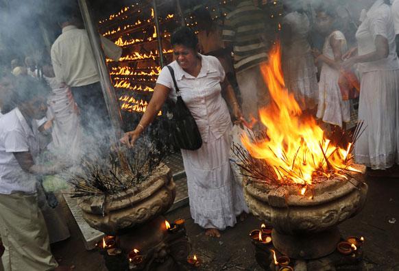 श्रीलंका के कोलंबो में एक बौद्ध मंदिर में पूजा-अर्चना करती हुईं एक श्रीलंकाई श्रद्धालु महिला।