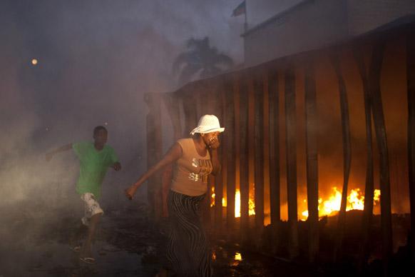 हैती में पोर्ट मार्केट में फैले आग के सामने से अपने मुंह और नाक को ढककर गुजरती हुई एक महिला।