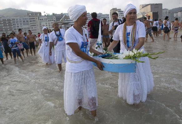 ब्राजील के रियो डी जेनेरियो में एक छोटे नाव में फूल रखकर समुद्र के देवता को अर्पित करने जाते हुए श्रद्धालु।