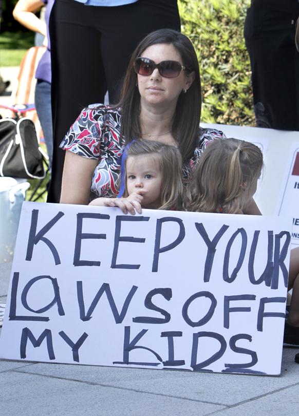 कैलिफ में अपने बच्चे के साथ एक रैली में शरीक होती महिला।