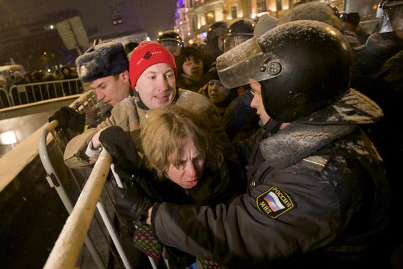 मास्को में रूसी पुलिस प्रदर्शनकारियों को रोकने की कोशिश करती हुई।