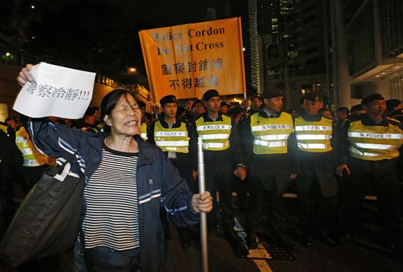 हांगकांग में पुलिस अधिकारियों के सामने सरकार विरोधी प्रदर्शन में शामिल एक प्रदर्शनकारी।