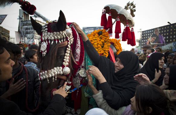 पाकिस्तान में एक परंपरा के दौरान घोड़े को सजाते हुए लोग।