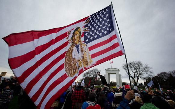 कनाडा-यूएस बॉर्डर पर प्रदर्शनकारी अमेरिकी झंडे को लहराते हुए।