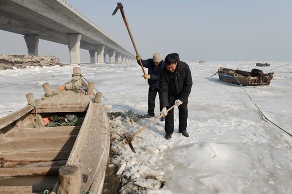 चीन के शेडांग प्रांत में एक फिशरमैन बर्फ में फंसी नाव को निकालते हुए।
