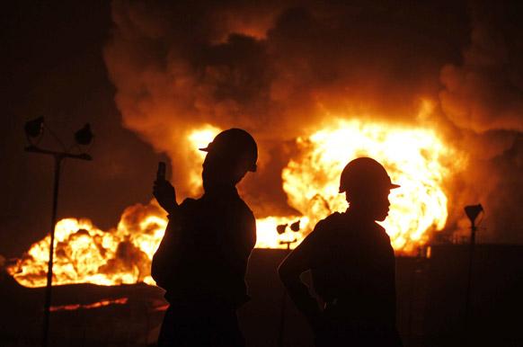 हजीरा इंडियन ऑयल डिपो में लगी आग की तस्वीर लेते हुए दमकलकर्मी।