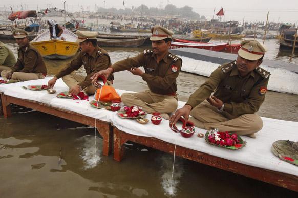 इलाहाबाद में गंगा के तट पर पूजा करते पुलिसकर्मी।