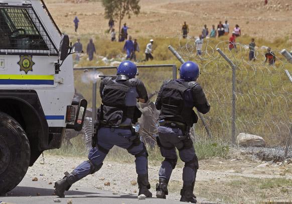 दक्षिण अफ्रीका में किसानों पर रबर फायरिंग करते पुलिसकर्मी।