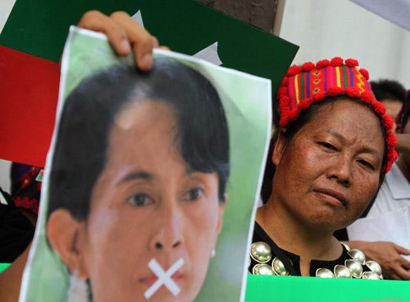 बैंकॉक में म्यामांर की विपक्षी नेता आंग सान सूकी के पोस्टर को लेकर प्रदर्शन करती एक महिला।