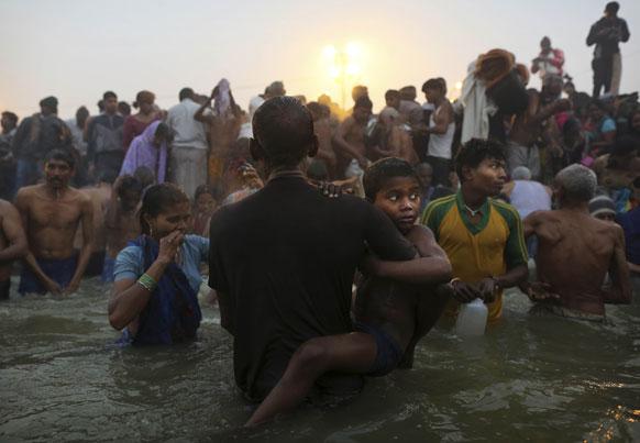 इलाहाबाद में महाकुंभ मेला के दौरान मकर संक्रांति के दिन अपने पिता के साथ संगम में डुबकी लगाने जाता एक बच्चा।