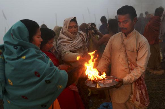 इलाहाबाद में गंगा, यमुना सरस्वती के संगम पर महाकुंभ मेला हिंदू पूजारी श्रद्धालुओं को आरती देते हुए।