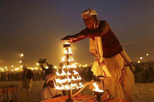 इलाहाबाद में संगम के तट पर संध्या पूजन के दौरान आरती करता हुआ एक पुजारी। 50 से अधिक दिनों तक चलने वाले महाकुंभ में लाखों श्रद्धालु रोज आस्था की डुबकी लगाने यहां आ रहे हैं।