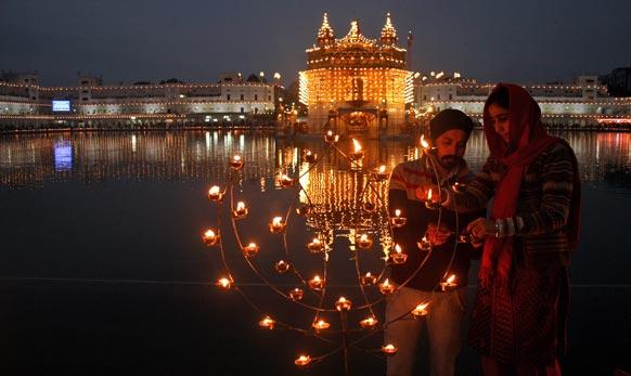 अमृतसर में गुरु गोविंद सिंह की जयंती मानने के लिए स्वर्ण मंदिर को प्रकाशित करते श्रद्धालु।