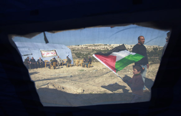 पश्चिमी तट पर एक शिविर के पास खड़ा फलीस्तीनी।