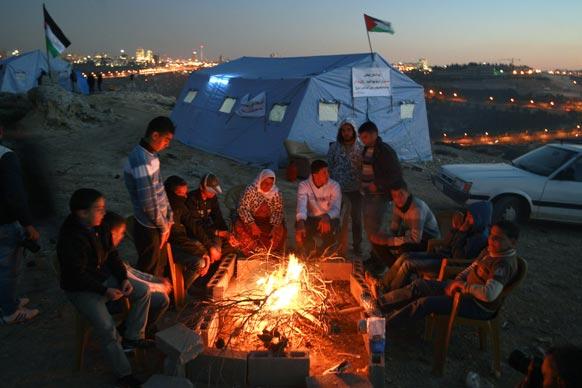 फिलीस्तीन के एक गांव में अलाव तापते स्थानीय लोग।