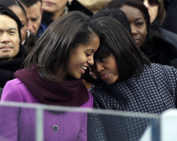 ओबामा के शपथ ग्रहण के दौरान अपनी पुत्री मालिया के साथ बातचीच करतीं मिशेल ओबामा।