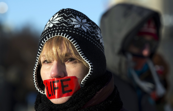 वाशिंगटन में मुंह पर पट्टी बांधकर प्रदर्शन करती एक मानवाधिकार कार्यकर्ता।