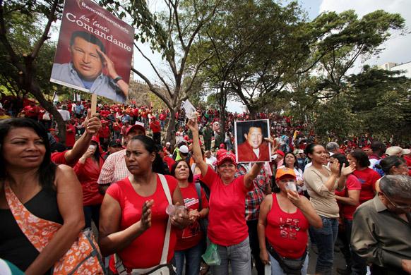 वेनेजुएला के कारकास में राष्ट्रपति हूगो शावेज के समर्थन में एक कार्यक्रम के दौरान प्रदर्शन करते लोग।