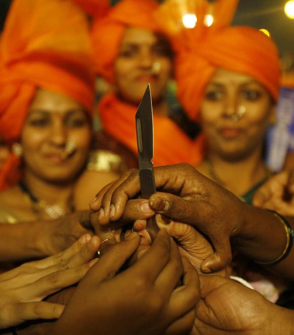 मुंबई में शिवसेना के स्थानीय नेताओं की ओर से बांटे जा रहे चाकुओं को लेने की तरफ हाथ बढ़ाती हुई महिलाएं।