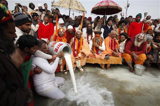 इलाहाबाद: महाकुंभ मेले के दौरान संगम तट पर जल में दूध को अर्पित कर पूजा अर्चना में लीन संत, धर्माचार्य व हिंदू श्रद्धालु। दुनिया के सबसे बड़े इस धार्मिक मेले महाकुंभ करोड़ों लोग आस्था की डुबकी लगाने आएंगे।