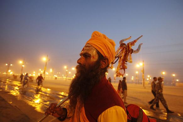 इलाहाबाद में महाकुंभ के दौरान संगम के किनारे विहंगम नजारे को निहारता त्रिशूल के साथ हिंदू संत।