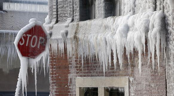 शिकागो में एक वेयरहाउस में आग लगने के बाद किसी को इस ओर जाने से रोकने के लिए स्टॉप का बोर्ड लगा दिया गया। स्टॉप बोर्ड और वेयरहाउस बिल्डिंग पर जमी बर्फ।