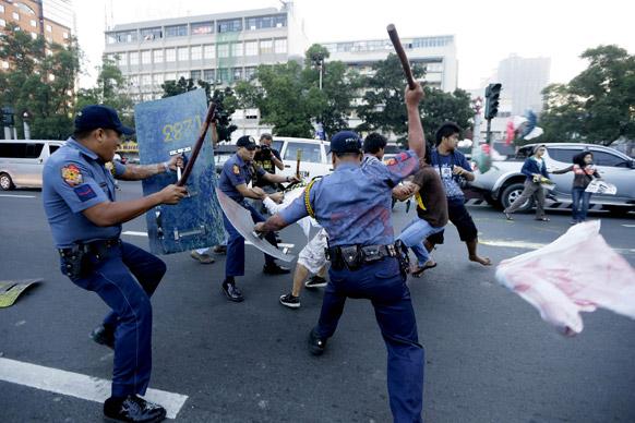 फिलीपींस की राजधानी मनीला में अमेरिकी दूतावास की मुहर पेंट कर प्रदर्शन करते प्रदर्शनकारियों को खदेड़ती पुलिस।