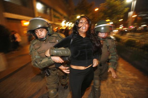 चिली के सेंटियागो में मपूची इंडियंस के समर्थन में प्रदर्शन करते प्रदर्शनकारी महिला को गिरफ्तार करती पुलिस। ये मपूची सरकार से जमीन लौटाने की मांग कर रहे हैं।