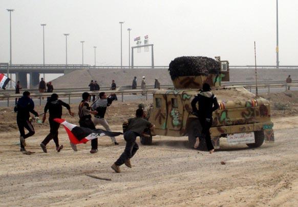 पश्चिमी बगदाद से 65 किमी. दूर फालुजाह में चेकिंग के दौरान हुए संघर्ष के बाद इराकी सैनिकों पर पत्थर फेंकते प्रदर्शनकारी।