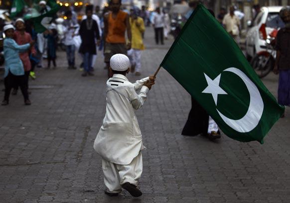 मुंबई में पैगंबर मोहम्मद की जयंती पर धार्मिक झंडे को लहराता एक भारतीय मुस्लिम किशोर।