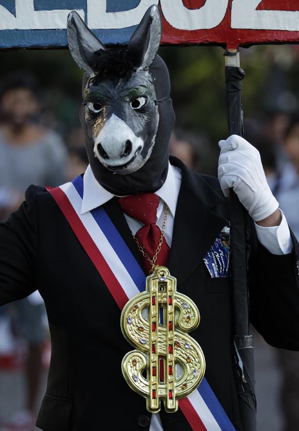 चिली के सेंटियागो में समिट के दौरान डंकी मास्क पहनकर राजनेताओं और भ्रष्टाचार के खिलाफ प्रदर्शन करता एक शख्स।