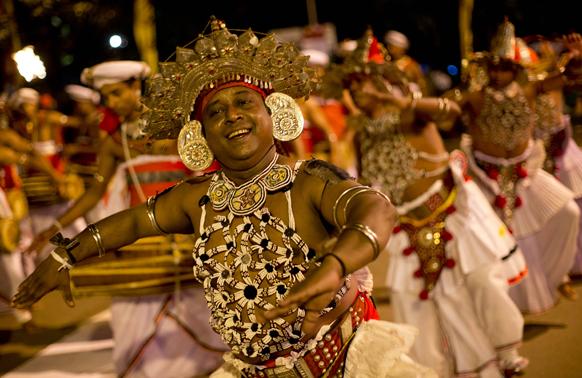 कोलंबो केलेनिया में सालाना बौद्ध महोत्सव पारंपरिक नृत्य की प्रस्तुति देते कलाकार।