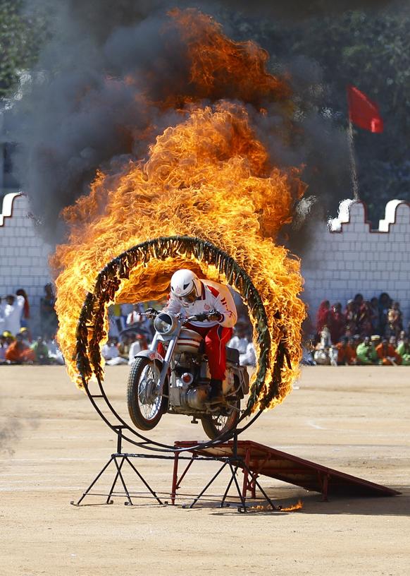 कर्नाटक की राजधानी बेंगलुरु में 64वें गणतंत्र दिवस समारोह के दौरान आयोजित एक समारोह में बर्निंग रिंग के बीच से अपनी बाइक को निकालता सेना का एक जवान।