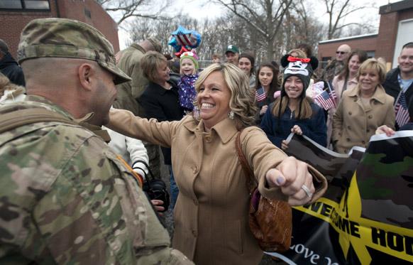 यूएस आर्मी रिजर्व सेंटर में वापसी पर 303वीं मिलिट्री पुलिस कंपनी के सदस्य और अपने पति सार्जेंट डी रोसिया का अभिवादन करती एमी डी रोसिया।