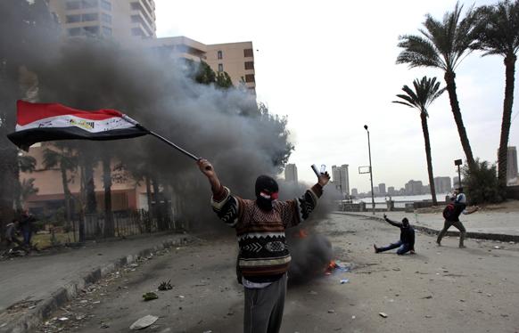 मिस्र के काहिरा में पुलिस-प्रदर्शनकारियों की झड़प के दौरान प्रदर्शनकारी राष्ट्रीय झंडे के साथ प्रदर्शन करते हुए।
