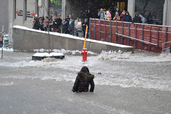 मोन्ट्रियल में मैक ग्रील विश्वविध्यालय के सामने एक महिला बाढ़ के पानी में।