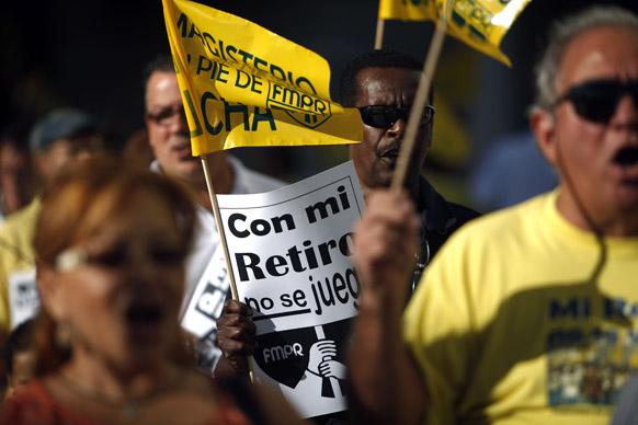 प्यूरटो रिको के सान जुआन में सरकारी पेंशन मुख्यालय के बाहर प्रदर्शन के दौरान आक्रोश जाहिर करते लोग।