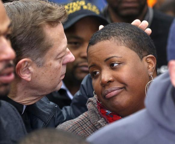 शिकागो में फादर माइकल फ्लेजर प्रेस कांफ्रेंस के दौरान एक महिला का सांत्वना देते हुए। इस महिला की बेटी की हत्या की गुत्थी सुलझाने के लिए लोगों से मदद की अपील की गई है।
