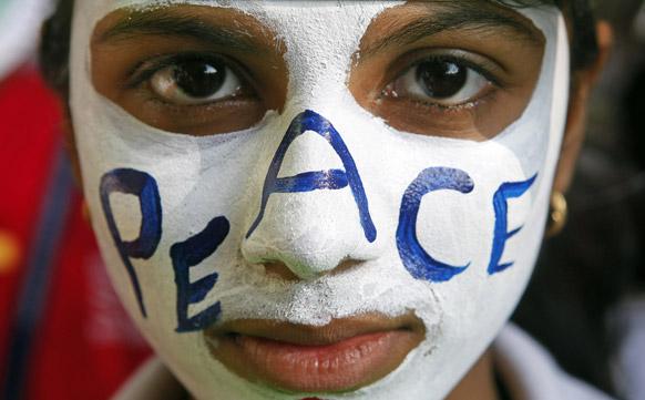 मुंबई में सांप्रदायिक सौहार्द्र एवं शांति के लिए निकाले गए मार्च में अपने चेहरे को रंगों से सजाए हुए एक कार्यकर्ता।