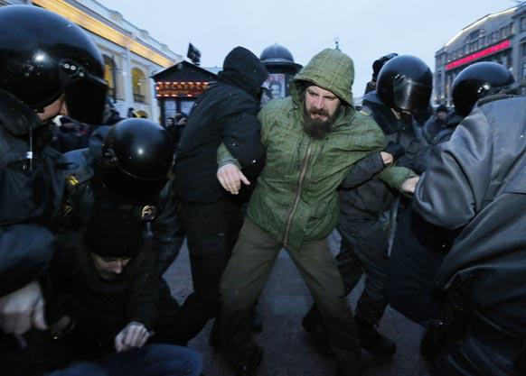 रूस के सेंट पीटर्सबर्ग में प्रतिबंधित एंटी क्रेमलिन प्रोटेस्ट के दौरान विपक्षी कार्यकर्ताओं को हिरासत में लेती पुलिस।