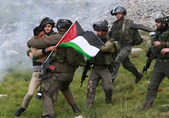 पश्चिमी तट पर एक फलीस्तीनी प्रदर्शनकारी को हिरासत में लेते इजरायल के सुरक्षाकर्मी।