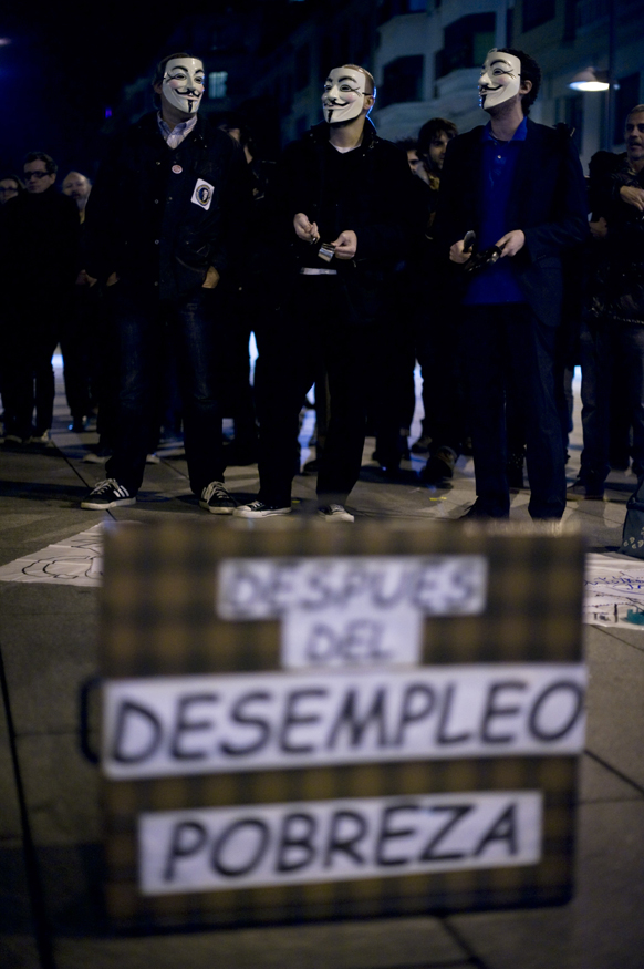 स्पेन के पामपलोना में पॉपुलर पार्टी कार्यालय के पास चेहर पर मुखौटा लगाकर प्रदर्शन करने पहुंचे प्रदर्शनकारी।