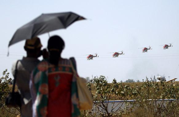 बैंगलोर के येलहंका एयरबेस पर एयरो इंडिया 2013 के रिहर्सल के दौरान भारतीय एयरफोर्स के हेलीकॉप्टर को देखते कपल।