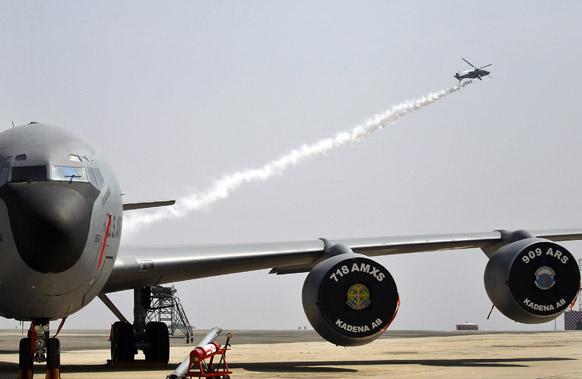 बैंगलोर के येलहंका एयरबेस पर एयरो इंडिया 2013 के रिहर्सल के दौरान भारतीय एयरफोर्स हेलीकॉप्टर यूएस एयरफोर्स केसी-3 के उपर उड़ान भरते हुए।