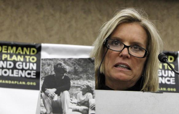 राबर्ट एफ केनेडी की बेटी केरी केनेडी अपने पिता की तस्वीर के साथ विरोध प्रदर्शित करती हुई।