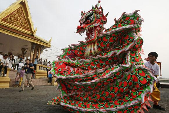 कंबोडिया के नोपेन्ह में रॉयल पैलेस के सामने ड्रैगन डांस करते कंबोडियन-चाइनीज लोग।