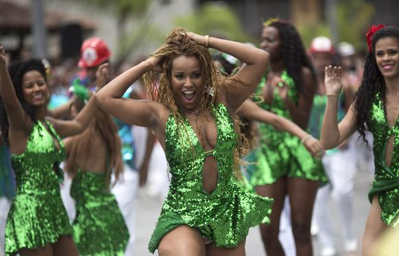 ब्राजील के रियो डि जेनेरो में प्री कार्निवल परेड के दौरान स्ट्रीट में डांस करती ग्रांड रियो संबा स्कूल की प्रतिभागी।