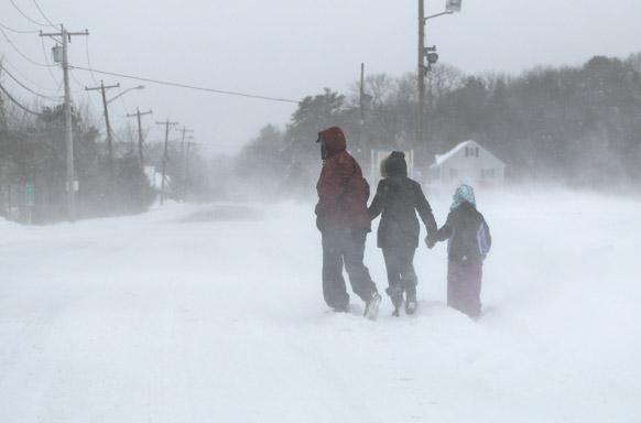 न्यू इंग्लैंड में भारी बर्फबारी के बीच अपने घर की तरफ जाता एक परिवार।