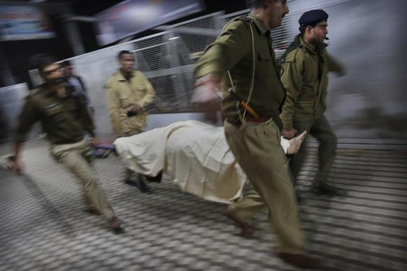 पुलिस के लोग मृतकों के शव को ले जाते हुए।